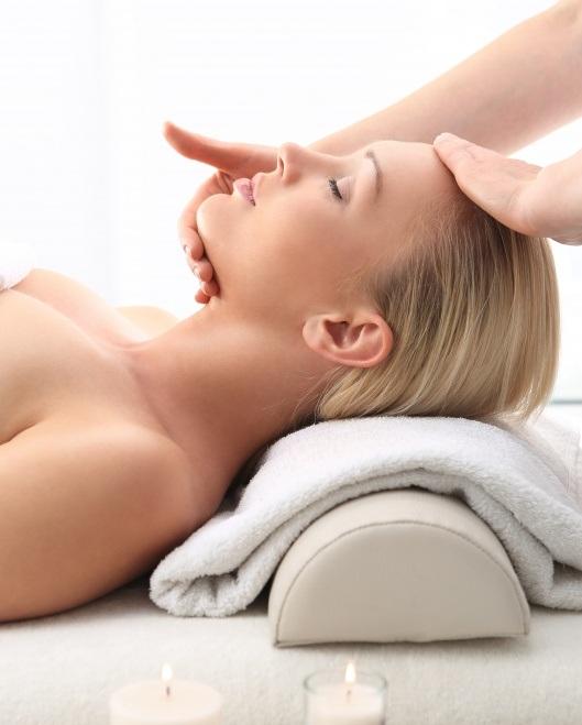 moteris, esanti šviesioje aplinkoje, užsimerkusi mėgaujasi veido masažu