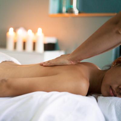 Jaukioje aplinkoje gulinti moteris, jai daromas nugaros masažas