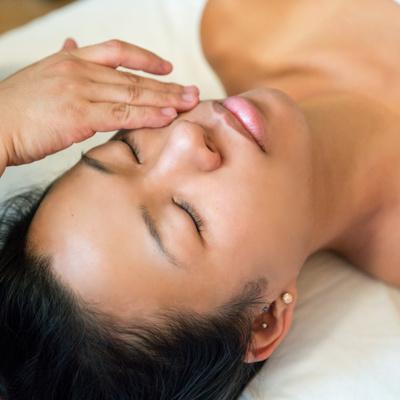 užsimerkusios moters veidas, jai daromas veido masažas